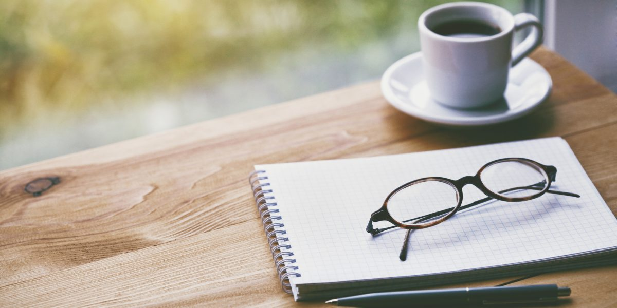 cup of fresh morning coffee with paper notebook, glasses and pen for writing