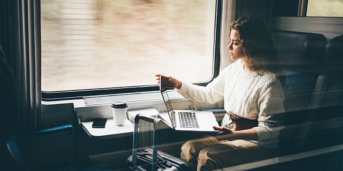 Freelancer girl working with laptop in the train, business travel or technology concept.